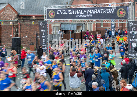 Warrington, UK. 16 September 2018.  The English Half Marathon, EHM, is celebrating it's 10th year in 2018. Rain had been forecast for the event but after an initial wet gathering the wet weather held off until the end of the run. Starting from a massed grid line-up in Winmarleigh Street, Warrington, Cheshire, England, the course follows the streets of the Town and concludes by crossing the red carpet finish through the iconic Golden Gates of Warrington Town Hall. It also hosts a 10k race at the same time Credit: John Hopkins/Alamy Live News - Stock Photo