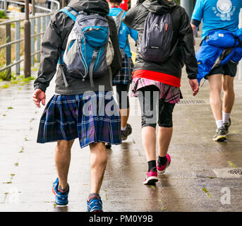 Leith, Edinburgh, Scotland, UK, 16th September 2018. Edinburgh Kilt Walk, the last of four kilt walks this year after those in Glasgow, Aberdeen and Dundee, sponsored by the Royal Bank of Scotland, takes place today. Walkers raise funds for a charity of their choice. There are three walk lengths: the full 24 miles from Holyrood Park to BT Murrayfield Stadium and two shorter walks of 15.5 and 5 miles. The kilt walkers reach The Shore at about Mile 14. A man wearing a kilt walks past - Stock Photo