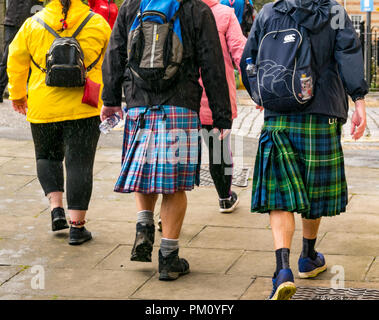 Leith, Edinburgh, Scotland, UK, 16th September 2018. Edinburgh Kilt Walk, the last of four kilt walks this year after those in Glasgow, Aberdeen and Dundee, sponsored by the Royal Bank of Scotland, takes place today. Walkers raise funds for a charity of their choice. There are three walk lengths: the full 24 miles from Holyrood Park to BT Murrayfield Stadium and two shorter walks of 15.5 and 5 miles. The kilt walkers reach The Shore in Leith at about Mile 14. Men carrying backpacks wearing kilts with swinging pleats walk past - Stock Photo