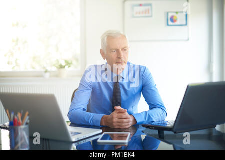 Shot of senior financial businessman looking thoughtfully while sitting at office in the offie. - Stock Photo
