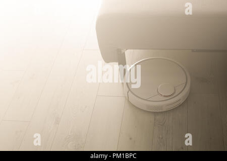 Robotic vacuum cleaner cleans the room from dust and debris, light from the window - Stock Photo