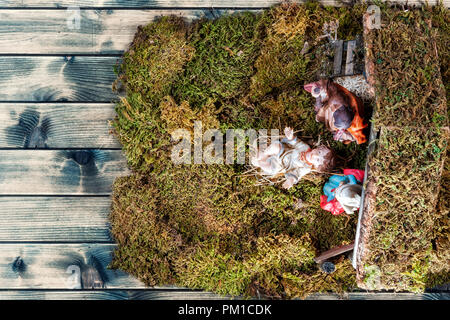 Top view of the Christmas Nativity scene. Hut with baby Jesus in the manger, with Mary and Joseph. On a vintage wooden table. - Stock Photo