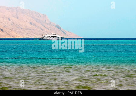 White ship in blue sea on mountain background in Red Sea - Stock Photo