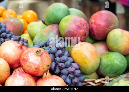 Fresh Mangos, Grapes, Pomegranetes & Oranges on Sale in Borough Market, Southwark, London UK - Stock Photo