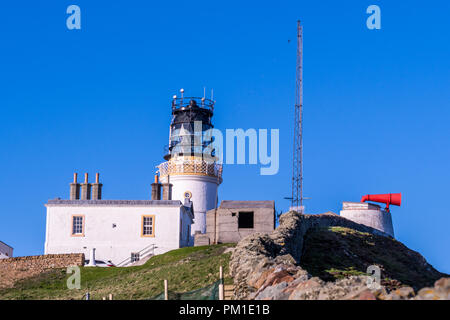 The old lighthouse at Sumburgh Head, on the southern tip of Shetland Isles on a clear blue evening. The red-painted ancient foghorn is still visible,  - Stock Photo