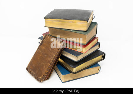 A stack of old books, staggered and angled away from the next book in the stack, set against a white background - Stock Photo