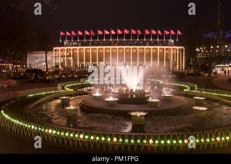 COPENHAGEN, DENMARK, MARCH 31, 2018: The Tivoli Concert Hall is illuminated at night, adorned with 19 Danish flags, as the fountains operate in the fo - Stock Photo