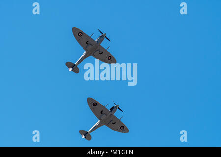 SOUTHPORT, UK JULY 8 2018: Two ex-RAF Spitfires perform a two ship display in the clear skies above Southport Beach for the annual airshow - Stock Photo