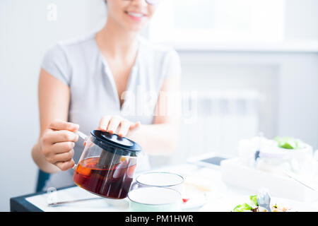 Young Woman Pouring Tea - Stock Photo