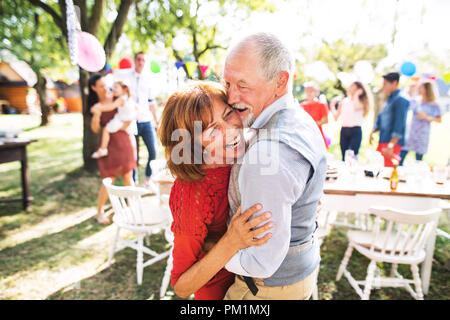 A senior couple dancing on a garden party outside in the backyard. - Stock Photo