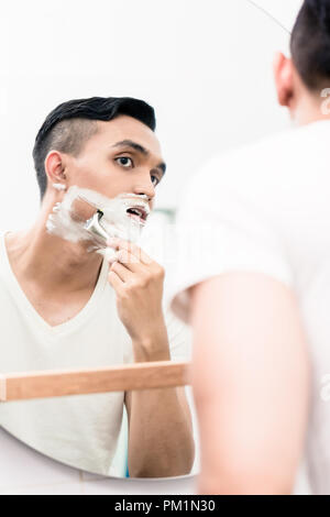 Man shaving in bathroom - Stock Photo