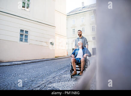 An adult son with senior father in wheelchair on a walk in town. - Stock Photo