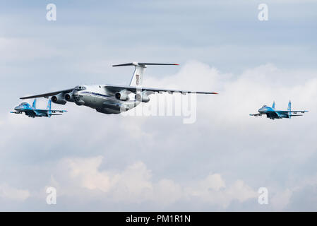 A Ilyushin Il-76 military transport aircraft of the Ukrainian Air Force is escorted by two Sukhoi Su-27 fighter jets. - Stock Photo