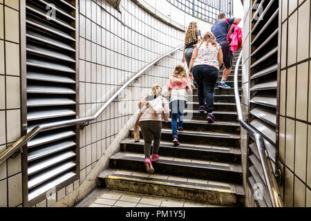 London England Great Britain United Kingdom Charing Cross Underground Station subway tube public transportation exit stairs woman girl climbing family - Stock Photo
