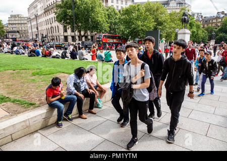 London England Great Britain United Kingdom Trafalgar Square plaza crowd Asian boy teen walking friends - Stock Photo