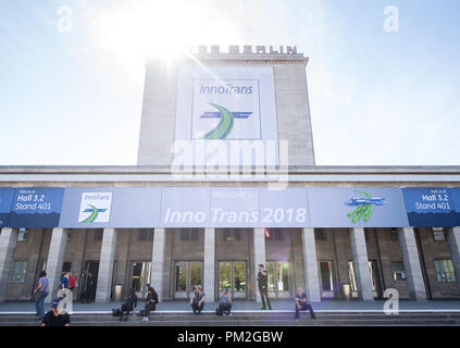 17 September 2018, Berlin: Several visitors are seated in front of the entrance to the InnoTrans traffic technology trade fair. From 18.09.2018, all innovations in traffic technology will be presented at Innotrans in 41 halls and on an open-air area with 3,500 running metres of rails. Photo: Fabian Sommer/dpa - Stock Photo