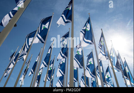 17 September 2018, Berlin: Several flags with the logo of the traffic technology fair InnoTrans are waving in the wind in front of the entrance to Messe Berlin. From 18.09.2018, all innovations in traffic technology will be presented at InnoTrans in 41 halls and on an open-air site with 3,500 running metres of rails. Photo: Fabian Sommer/dpa - Stock Photo