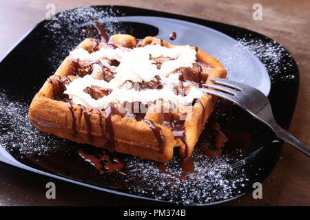 Closeup of homemade Belgian waffles with whipped cream, chocolate sauce and raspberries on black plate. Sweet dessert. - Stock Photo