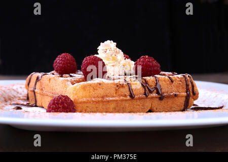 Closeup of homemade Belgian waffles with whipped cream, chocolate sauce and raspberries on white plate. - Stock Photo