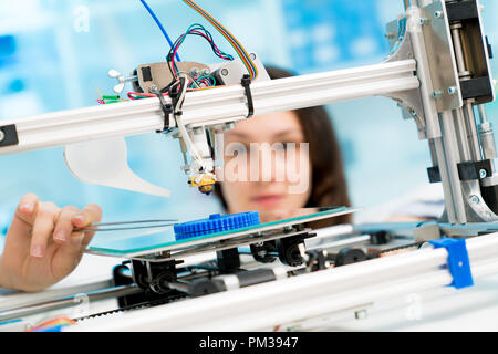 female student or laboratory assistant in the automation laboratory is debugging the work of the 3d printer. 3d printer is a device for modeling objec - Stock Photo