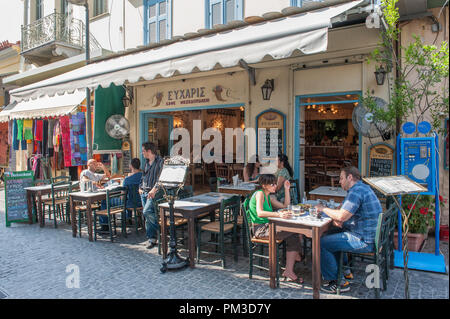 Outdoor restaurant at Plaka in Athens. This picturesque neighborhood of the old historical Athens located between Acropolis and Syntagma - Stock Photo
