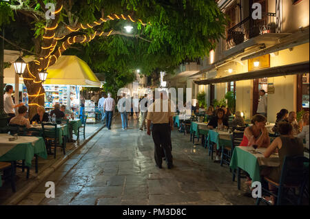 Outdoor restaurant at Plaka by night in Athens. This picturesque neighborhood of the old historical Athens located between Acropolis and Syntagma - Stock Photo
