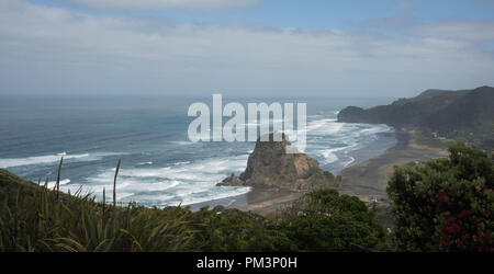 Elevated view over the volcanic black sand Piha Beach with the Tasman Sea waves and large Lion Rock landmark in Auckland, New Zealand - Stock Photo
