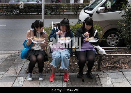 Three Japanese girls eating junk food on Omotesando street, Tokyo, Japan, Asia. Female friends having quick lunch - Stock Photo