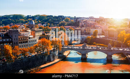 Skyline with bridge Ponte Vittorio Emanuele II and classic architecture in Rome, Vatican City scenery over Tiber river. Autumn view with red foliage. - Stock Photo