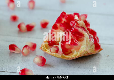 Sliced pomegranate and grains on wooden table,close up,detail, - Stock Photo