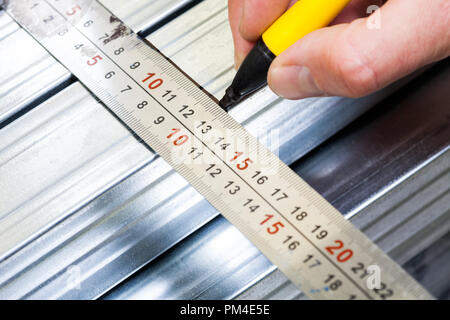 Person marking a  measurement on a metal stud with marker pen while constructing plasterboard frame - Stock Photo