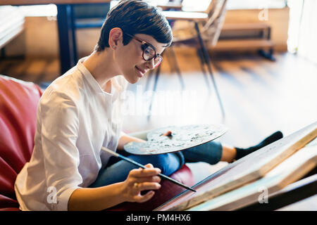 Female artist painting with palette and paintbrush - Stock Photo