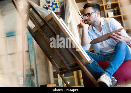Portrait Of Male Artist Working On Painting In Studio - Stock Photo