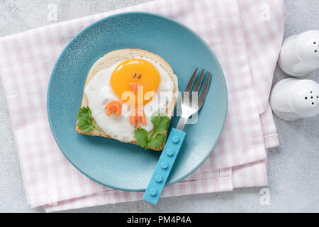 Breakfast for kids. Egg toast with funny cute food art on a blue plate. Top view - Stock Photo