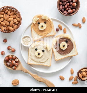 Nut butter toast in shape of cute funny bear for kids served on a white plate. Top view. Creative food art, breakfast for kids, school lunch concept - Stock Photo