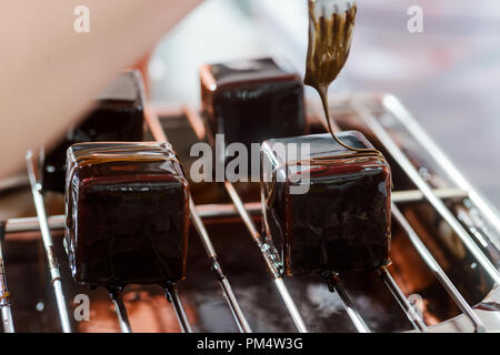 Decorating mousse cakes with caramel - Stock Photo