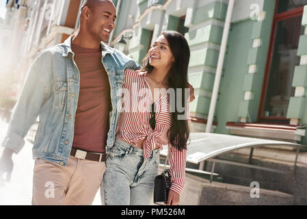 Romantic Relationship. Young diverse couple walking on the city street hugging looking at each other talking smiling happy - Stock Photo
