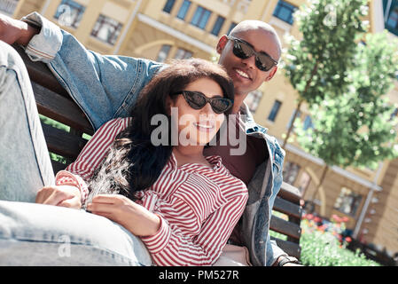 Romantic Relationship. Young diverse couple wearing sunglasses sitting on bench on the city street smiling relaxed close-up - Stock Photo