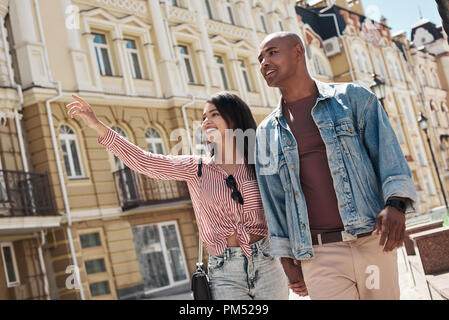 Romantic Relationship. Young diverse couple walking on the city street holding hands sightseeing smiling happy - Stock Photo