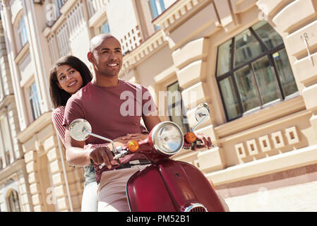 Romantic Relationship. Young diverse couple riding bike on the city street together smiling happy - Stock Photo