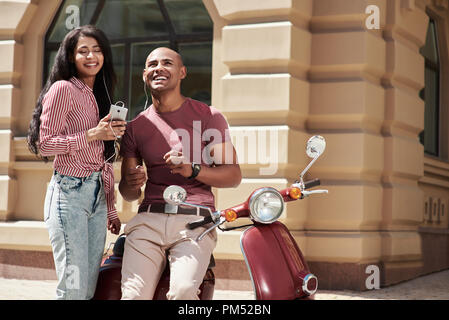 Romantic Relationship. Young diverse couple wearing earphones sitting on bike on the city street listening to music on smartphone smiling joyful - Stock Photo