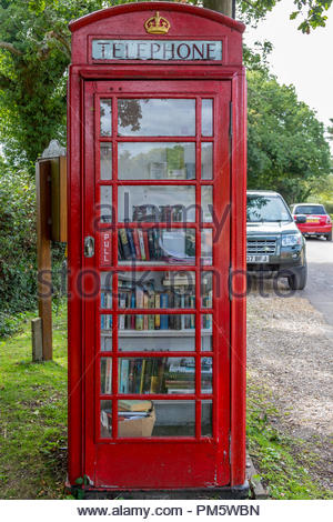An old BT red telephone box in use as an informal library in the New Forest village of Fritham, Hampshire, UK - Stock Photo