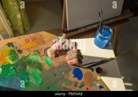 Artist with hand stained of paint holding his palette full of mixed colors. Painter ready to work next to a bright window. - Stock Photo