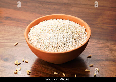 CloClose up of Pearl Barley in a Earthen Bowl on Wooden Background Close up of Pearl Barley in a Earthen Bowl on Wooden Background - Stock Photo