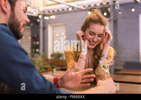 Young girl closing her eyes while feeling too drunk in the bar - Stock Photo