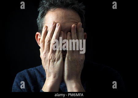 Portrait of man on black background, stressed, hands on face Stock Photo