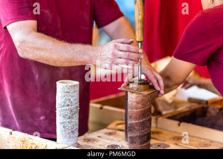 Hungarian Chimney cakes prepared in street market - Stock Photo