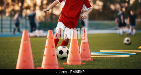 Soccer Drills: The Slalom Drill. Youth soccer practice drills. Young football player training on pitch. Soccer slalom cone drill. Boy in red jersey - Stock Photo