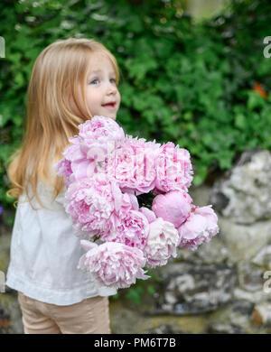 Blonde girl holding fresh peonies bouquet - Stock Photo