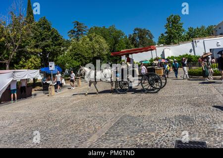 Ronda, Spain - 21 June 2017: People walk past a horse drawn cart in Ronda, Spain - Stock Photo